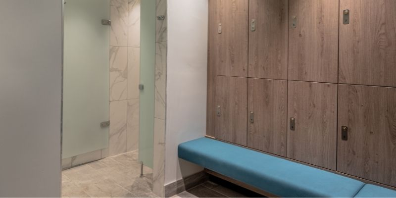 Stratton House: Image of a bespoke wooden changing room locker system with integrated light blue bench seating, designed and installed by Crown Sports Lockers.