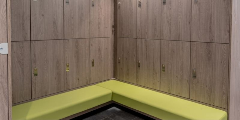 Stratton House: Image of a bespoke wooden changing room locker system with integrated lime green bench seating, designed and installed by Crown Sports Lockers.